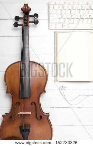 keyboard computer with notebook and violin on white wood background