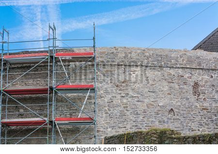 Old city walls with scaffolding against blue sky.