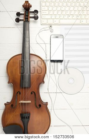 violin with music paper note keyboard computer dvd disc and smart phone on white wood background