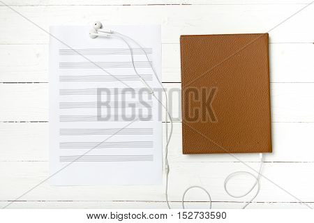 top view of earphone music staff paper and book on white wood background