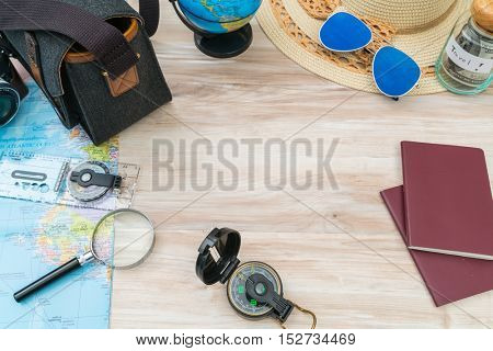 Travel preparation : compass, money, passport, road map ,hat,sunglasses,magnifying glass on wooden table