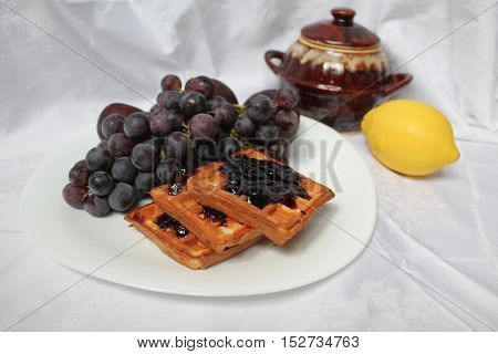 appetizing healthy meal sweet blue grapes, plums, leamon, cookies, jam and honey