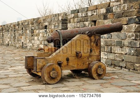 An old weathered cannon on a wooden cart on the Nanjing city wall on an overcast day in Jiangsu province China.