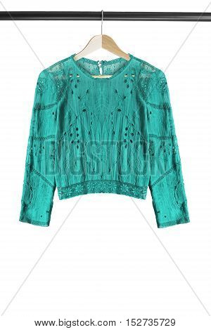 Ethnic cyan blouse on wooden clothes rack isolated over white