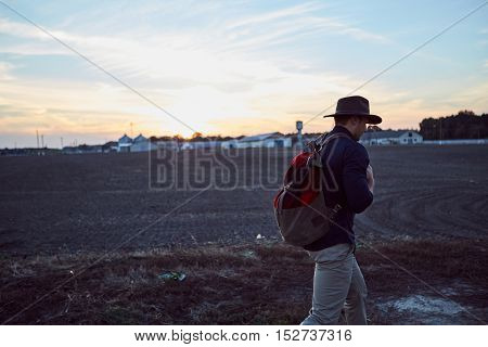 Adventurous man wearing hat and backpack strolling around the empty field