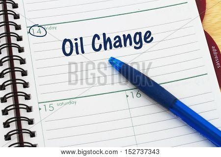 Scheduling your car's oil change appointment A day planner with blue pen with text Oil Change