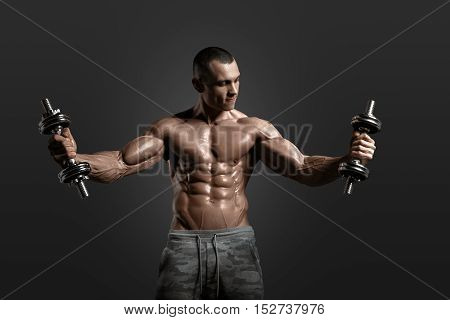Muscular athletic bodybuilder model posing after exercises in gym