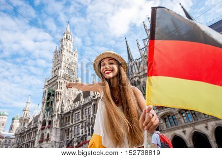 Portrait of a young female tourist with german flag standing on the central square with town hall building on the background in Munich. Having a great vacation in Germany