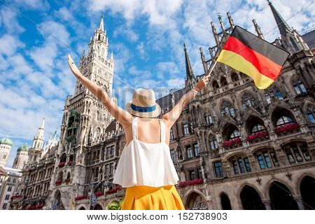 Young female tourist with raised hands holding german flag on the central square in front of the town hall building in Munich