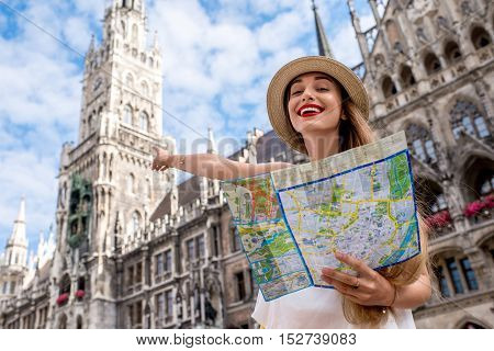 Portrait of a young female tourist with map standing on the central square in front of the famous town hall building in Munich