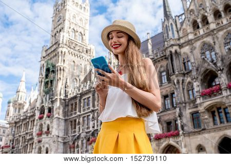 Young female tourist using mobile phone on the central square in front of the famous town hall building in Munich