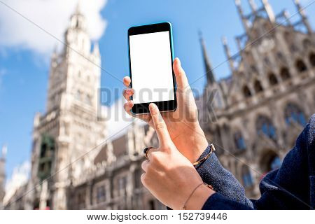 Holding a smart phone with white screen on the central city square background in Munich, Germany