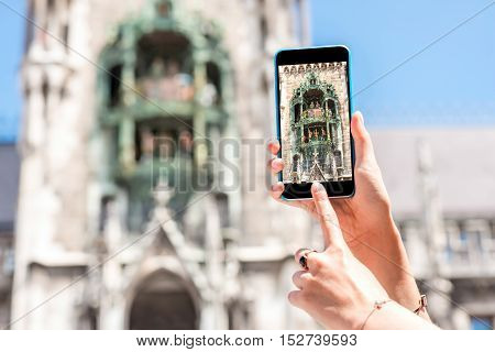 Photographing with smart phone a famous clock on the town hall's tower in Munich city, Germany