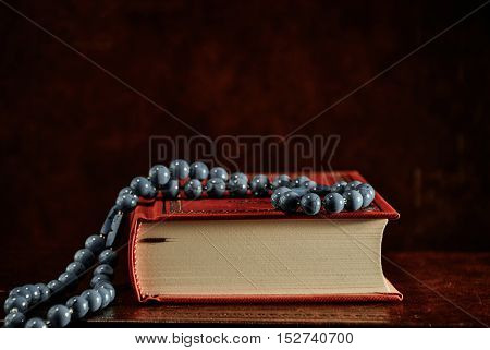 Rosary beads and red Holy Bible on table