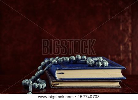 Rosary beads and prayer books on table