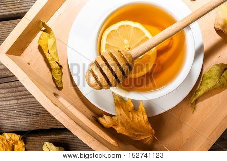 Autumn warming ginger tea with honey and lemon on a tray, a cozy breakfast or snack. At the rustic wooden table, close view. With autumn yellow leaves around.
