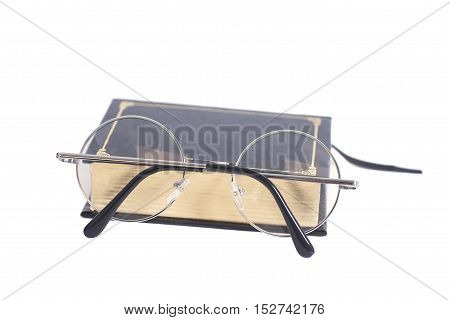 Round Eyeglasses and book isolated on white
