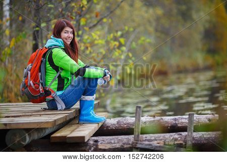 Young brunette with backpack sitting on bridge by pond