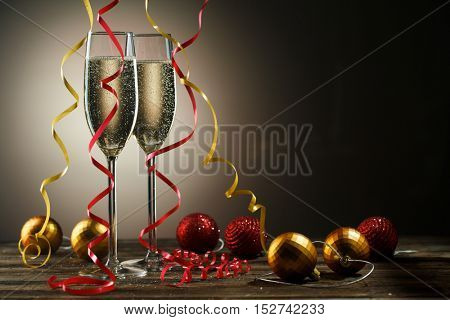 Two glasses of champagne with bubbles and decorative Christmas balls