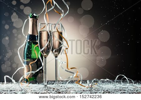 Champagne bottle and two wineglasses on table covered snow