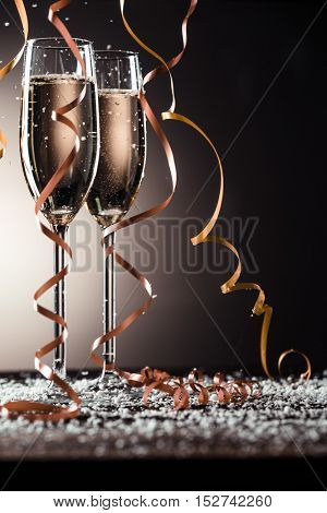 Champagne glasses with ribbons and snowflakes on dark background