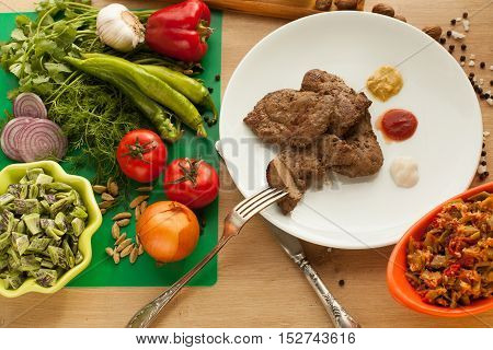Roast meat served with ketchup, mayonnaise and mustard, sliced piece of meat hanging on a fork. Cooked liver with spices. Vegetarian food against meat. Vegetables vs meat.