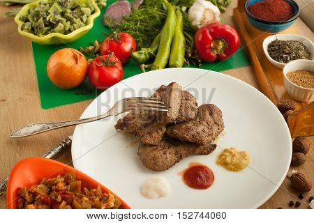 Roast meat served with ketchup, mayonnaise and mustard, sliced piece of meat hanging on a fork. Cooked liver with spices and salad on white plate standing on the table. Vegetables vs meat.