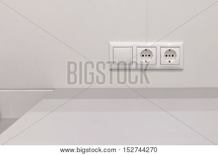 two electrical sockets with a switch on a white wall