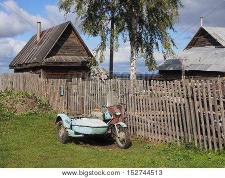 View of traditional village house with wooden fence. Old motorcycle with sidecar. Blue sky clouds