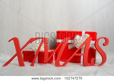 Word Xmas And Christmas Gifts On A White Carpet