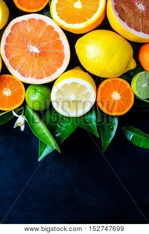 Citrus background. Assorted fresh citrus fruits with leaves. Lemon, orange lime, grapefruit mandarin. Harvest concept. Top view. Black stone rustic background. Copy space