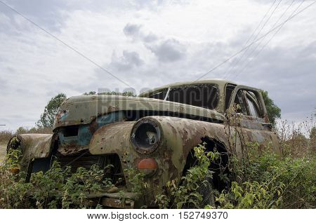 Old abandoned rusty car in autumn on sky background