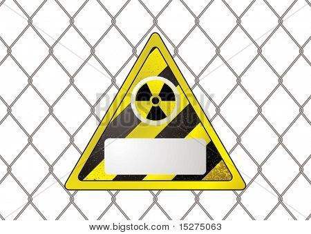 triangular nuclear sign attached to a wire fence with copy space