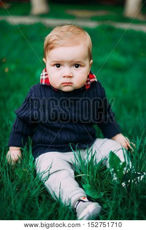 Beautiful Baby Boy Sitting Among Green Grass On Spring Lawn