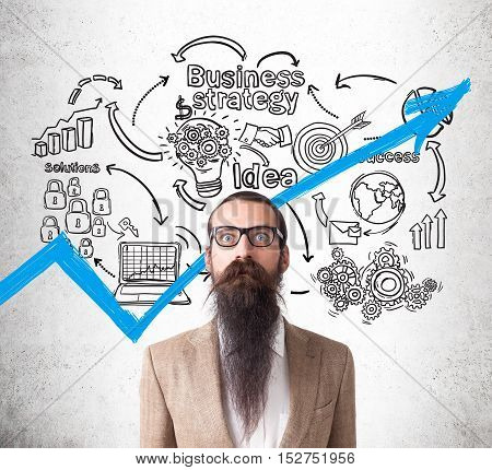Baffled man in glasses with long beard is standing against concrete wall with business strategy sketches on it. Concept of successful manager