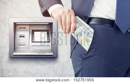 Businessman putting stack of dollars into his pocket and standing near ATM machine in concrete wall. Concept of salary.