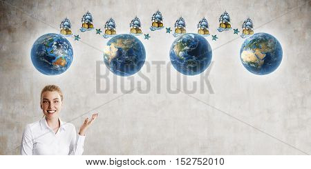 Smiling blond girl showing four planets connected by sail ships on concrete wall. Mock up. Concept of time travel.