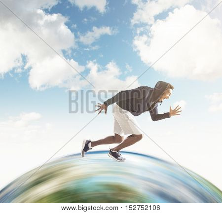 Close up of African American guy running on huge globe surface. Concept of the fastest man on Earth. Mock up. Toned image.