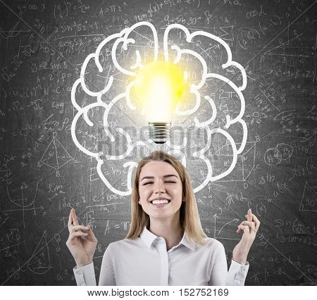 Close up of woman with crossed fingers standing against blackboard with light bulb and brain sketches surrounded by formulas. Concept of solution finding.