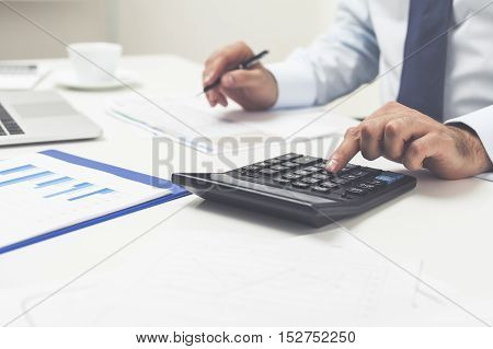 Close up of man's hands. He is using his calculator and writing numbers down. Concept of accounting work.
