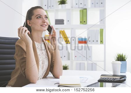 Dreamy girl in beige is talking on her cell phone in office and looking into space with cloudy eyes. Concept of making your dreams come true