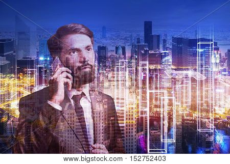 Portrait of bearded businessman on his phone standing against large night cityscape. Double exposure. Toned image