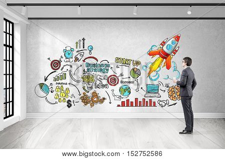Side view of businessman with cup of coffee looking at colorful startup sketch on concrete wall. Concept of strategic thinking. 3d rendering.