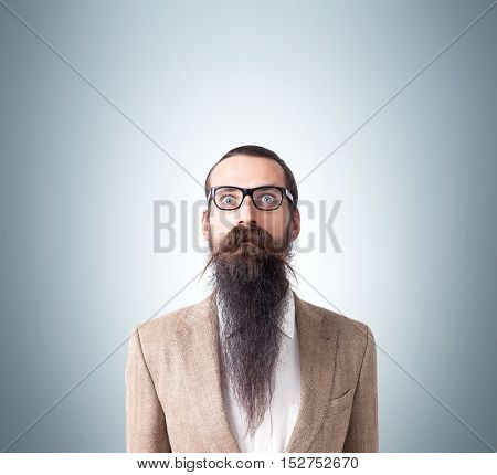 Baffled man wearing glasses and long beard is standing against gray background. Concept of eccentric person. Mock up