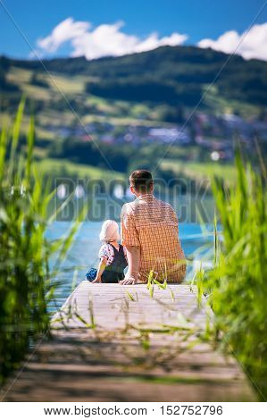 Father With His Son Sitting On Jetty And Enjoying The View On The Sea