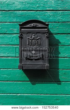 black mailbox on a green wooden boards