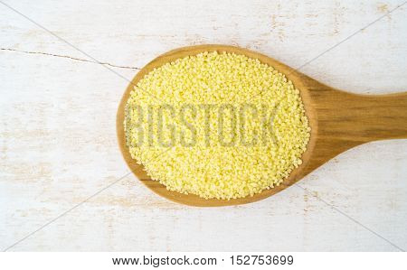 Couscous in wooden spoon on white background horizontal selective focus