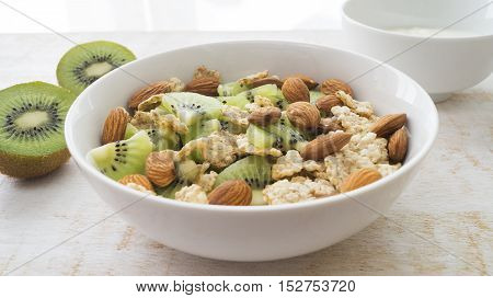 Whole grain cereal with kiwi and almond in white bowl and yogurt. Healthy breakfast. Health and diet concept selective focus close up horizontal