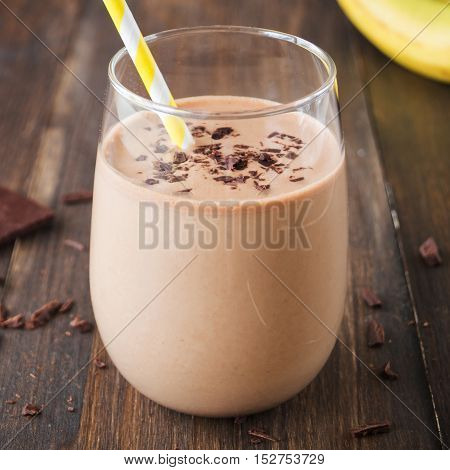 Chocolate banana smoothie in glass with paper straw on wooden background selective focus