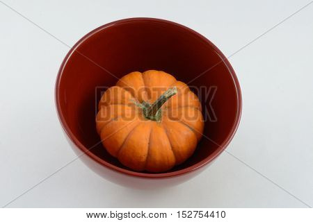 Small raw pumpkin in red bowl against white background